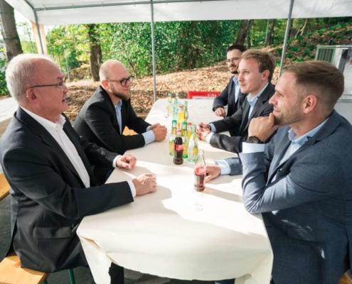 männer sitzen an tisch mit getränken
