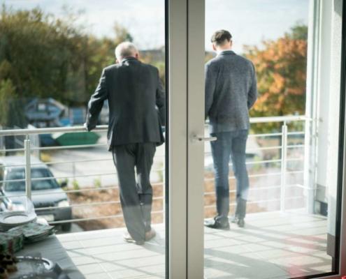 zwei männer schauen vom balkon