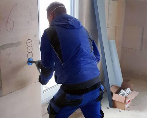 mann im blaumann arbeitet an wand