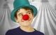 junge mit roter clownsnase und türkisem glitzerhut