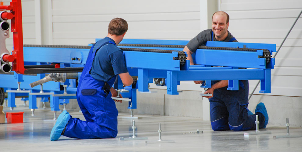 two employees assemble conveyor system