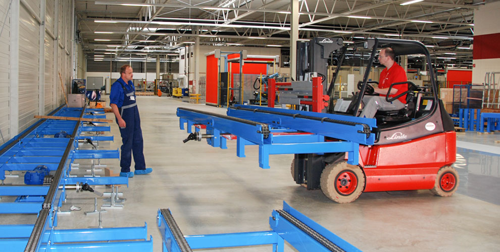 red lift truck transports blue parts of a conveyor system