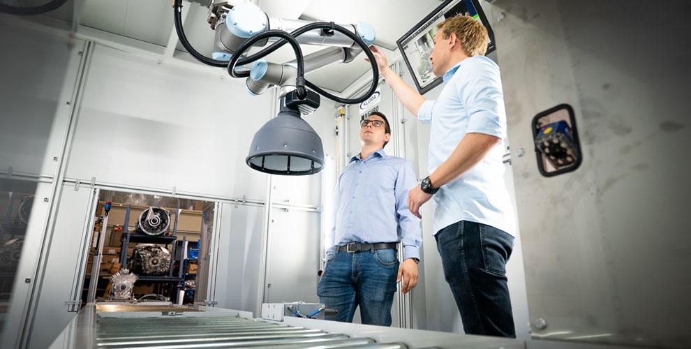 mitarbeiter prüfen roboter über förderanlage