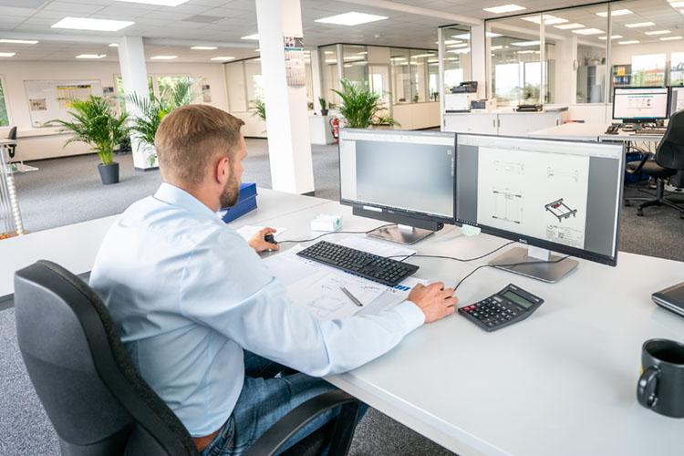mitarbeiter an schreibtisch mit zwei bildschirmen