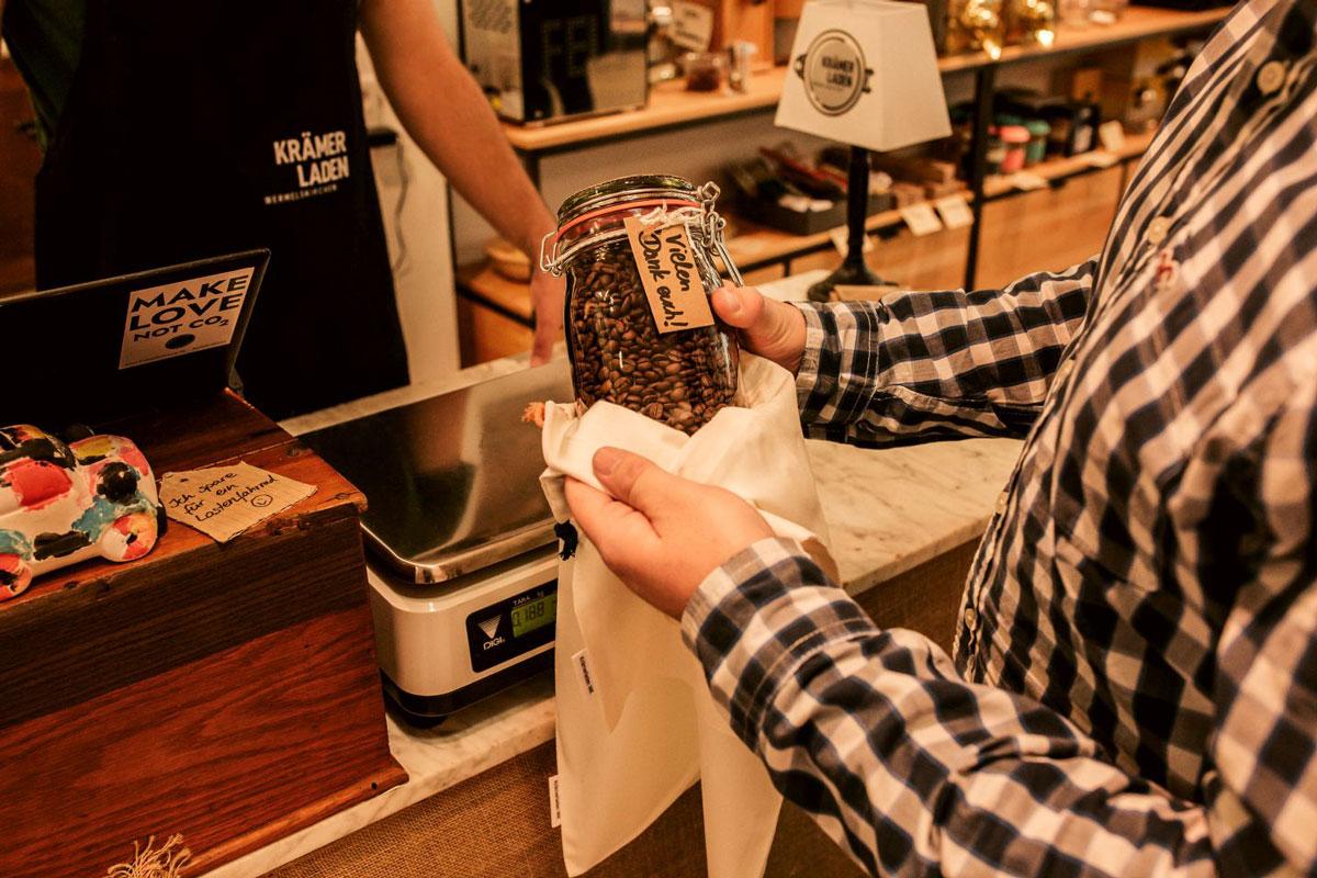 mann im karierten hemd hält einmachglas mit kaffeebohnen