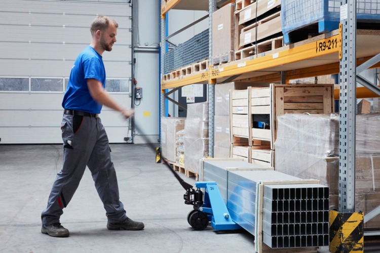 man moves blue pallet truck into storage