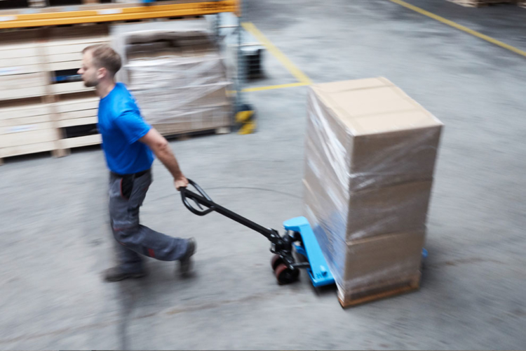 man pushes blue pallet truck into storage