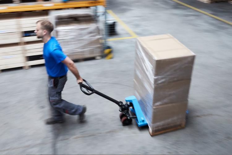 mann schiebt blauen hubtisch mit paketen
