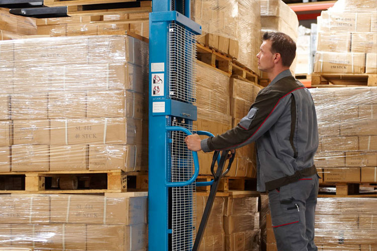 warehouse staff operating high-lift trucks with pallets and packages