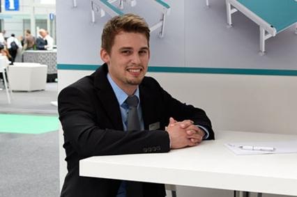 mann im anzug sitzt mit gefalteten händen am tisch